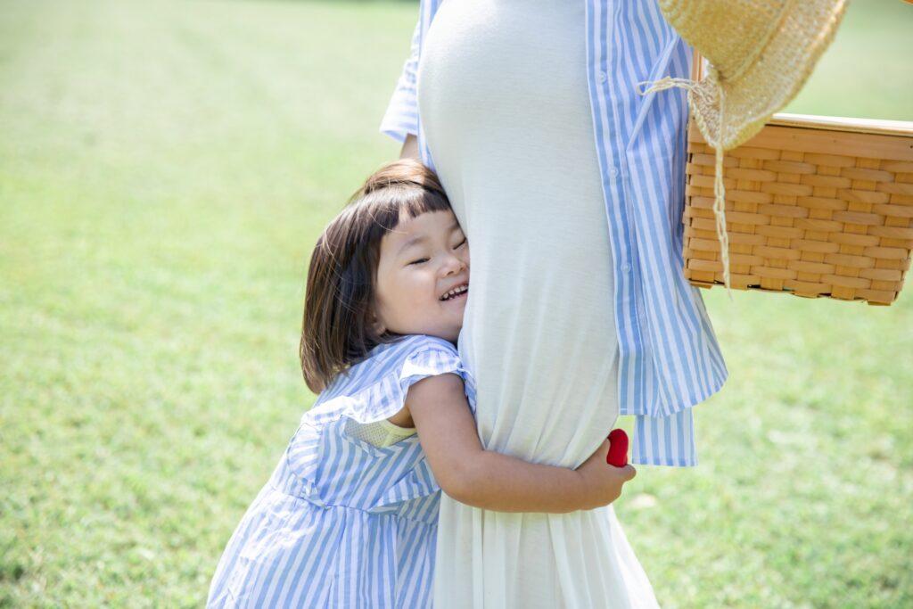 妊活中女性(母親)に抱きつく子供(女の子)