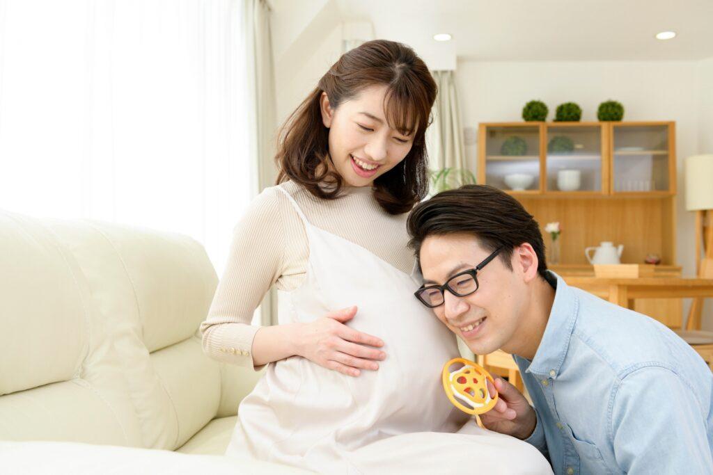 妊娠女性のお腹に耳を当てる旦那さん