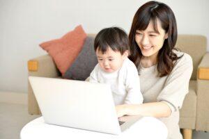 パソコンの前で作業する母親と赤ん坊