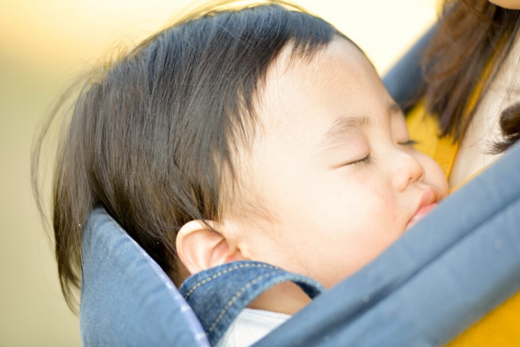 母親の背中で昼寝をする男の子