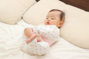 寝室のベッドで寝転がる赤ちゃん