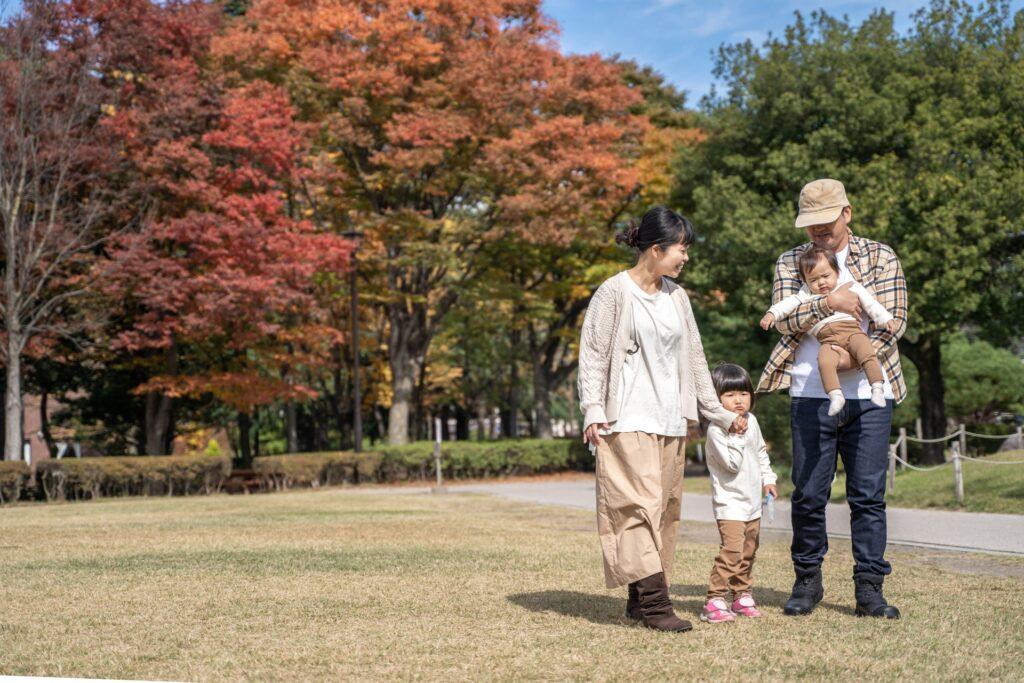 秋の公園で遊ぶ家族