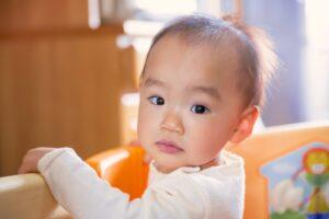 つかまり立ちする赤ちゃん(女の子)の写真