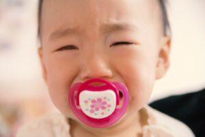 おしゃぶりを咥えて泣く赤ちゃん