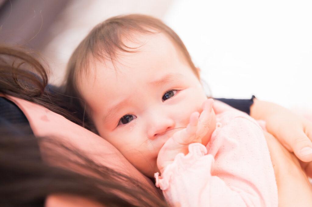 お母さんの腕の中で涙が溢れる赤ちゃん