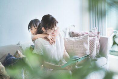 ソファに座って絵本を読む母親と子供