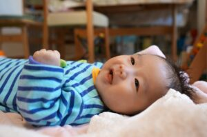 リビングで寝そべるロンパースを着た笑顔の赤ちゃん
