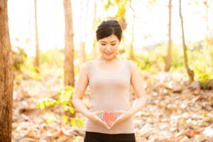 お腹の前でハートを持つ妊活女性