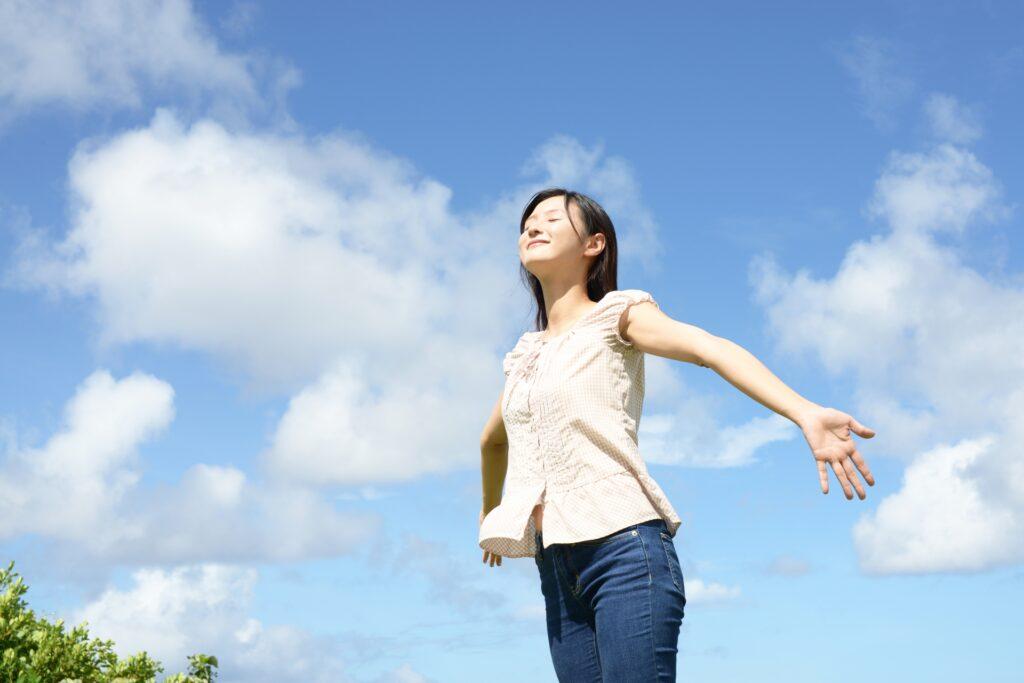 両手を広げて心身をリフレッシュする女性