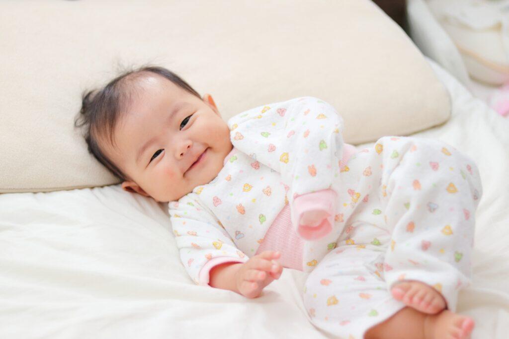 ベット寝転がって笑顔を見せる赤ちゃん