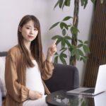 パソコンの前で手指差しポーズを取る妊婦
