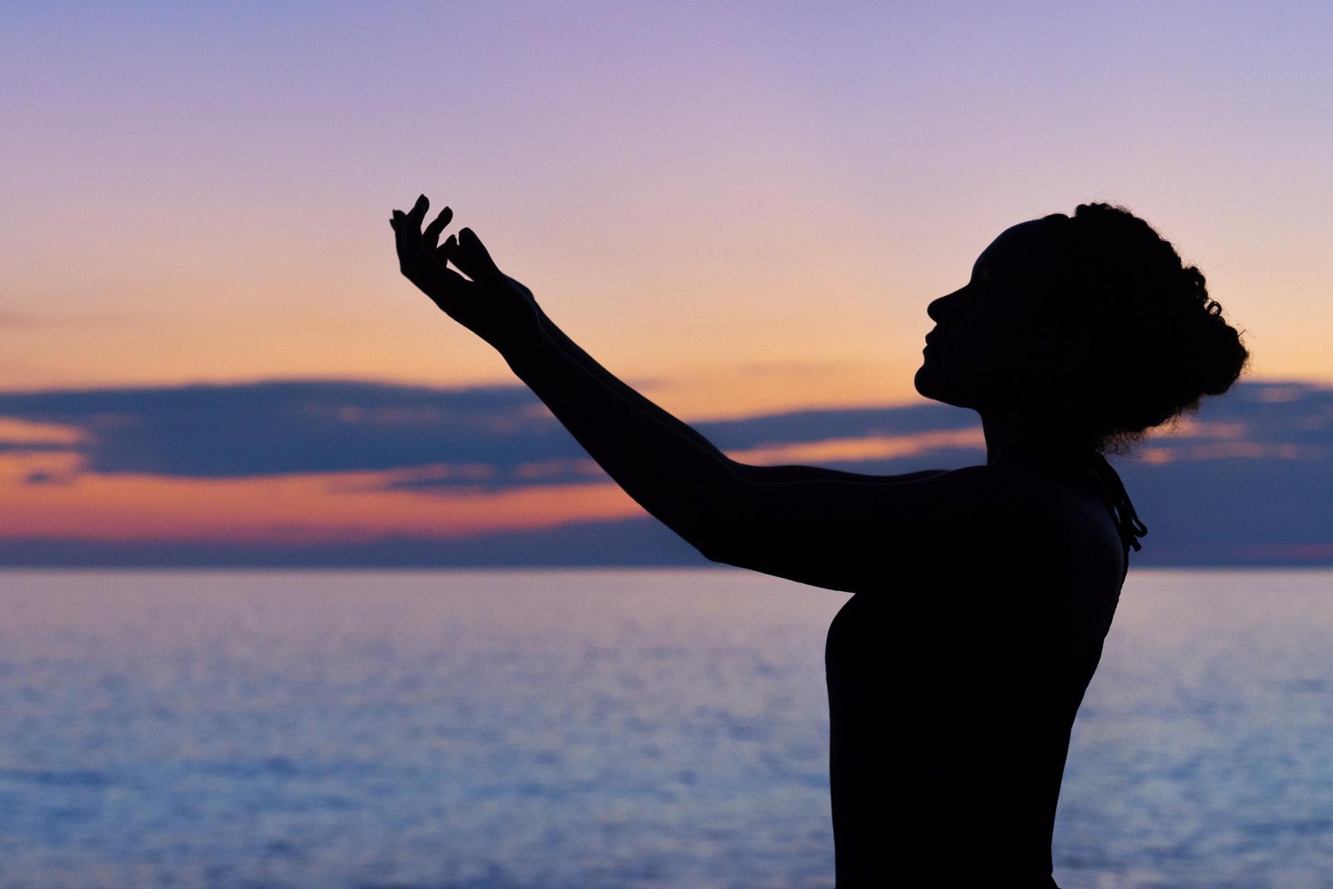 海で両手を上げる女性