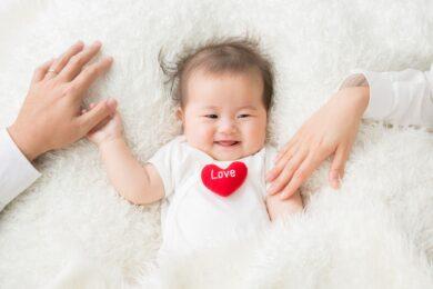 笑顔の赤ちゃんと手を繋ぐ両親