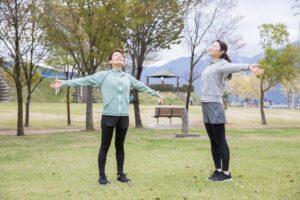 公園で深呼吸を行う女性
