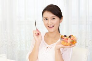 フルーツを食べようとする女性